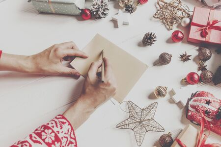 hands holding pencil and writing a letter wish list to santa claus with space for text. merry christmas and happy new year. child hand in pajamas and craft and presents and ornaments on white wood