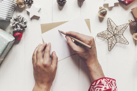 kind schrijft brief aan de Kerstman bovenaanzicht. kid handen houden potlood en het maken van de wens lijst en papier met kerstversieringen en ornamenten en presenteert op wit hout. ruimte voor tekst