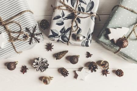 moderne kerst plat lag samenstelling. stijlvol verpakt presenteert met ornamenten en kegels anijs op rustieke witte hout, bovenaanzicht.