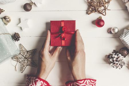 Kerstmis en gelukkig Nieuwjaar plat leggen. handen met rode huidige geschenkdoos op rustieke witte hout met presenteert en ornamenten, bovenaanzicht. seizoensgroeten. fijne feestdagen, moderne kerstkaart