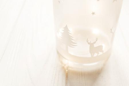 vrolijk kerstfeest. lantaarn met herten en boom met verlichting lichten op witte houten achtergrond met ruimte voor tekst. seizoensgebonden wenskaart. fijne vakantie. Kerstmis