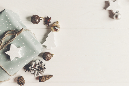 merry christmas concept, flat lay. stylish presents and gifts with ornaments cones anise on rustic white wood top view, space for text. seasonal greetings. happy holidays. xmas card