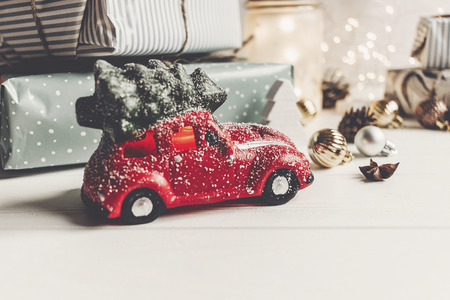 moderne kerst ornamenten en auto speelgoed met boom, presenteert kegels anijs op witte houten achtergrond. vrolijk kerstfeest concept. seizoensgroeten. fijne feestdagen, kerstkaart, hygge Stockfoto