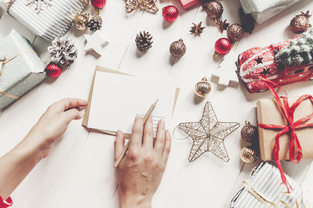 hands holding pencil and writing a letter wish list to santa claus flat lay with space for text. merry christmas and happy new year top view. hand craft and presents and ornaments on white wood