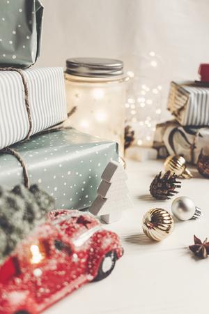 vrolijk kerstfeest en een gelukkig nieuwjaar. modern presenteert, ornamenten, auto speelgoed met boom, anijs kegels en lichten op rustieke witte houten achtergrond. seizoensgroeten. fijne feestdagen, kerstkaart