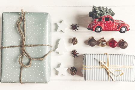 vrolijk kerstfeest concept, plat lag. moderne presenteert met auto met boom, ornamenten op rustieke witte houten bovenaanzicht. seizoensgroeten. Stockfoto