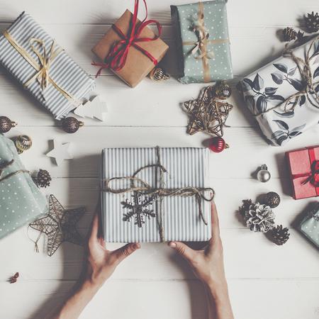 vrolijk kerstfeest en gelukkig nieuwjaar plat liggen. handen geven rustieke huidige vak op wit hout met geschenken en ornamenten, bovenaanzicht. seizoensgroeten. fijne feestdagen, moderne kerstkaart Stockfoto