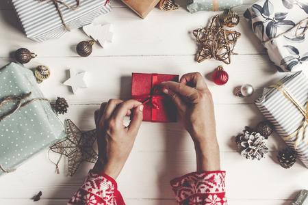 vrolijk kerstfeest en gelukkig nieuwjaar plat liggen. handen inwikkeling rode huidige geschenkdoos op rustieke witte hout met presenteert en ornamenten, bovenaanzicht. seizoensgroeten. fijne feestdagen, moderne kerstkaart Stockfoto