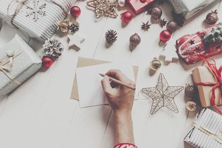 handen met potlood en het schrijven van een brief verlanglijstje voor de kerstman met ruimte voor tekst. vrolijk kerstfeest en een gelukkig nieuwjaar. kind hand in pyjama en ambachtelijke en presenteert en ornamenten op wit hout