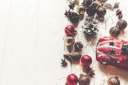 moderne kerst plat lag samenstelling. stijlvolle speelgoedauto met boom en ornamenten kegels anijs en lichten op rustieke witte hout, bovenaanzicht. seizoensgroeten. fijne feestdagen, kerstkaart