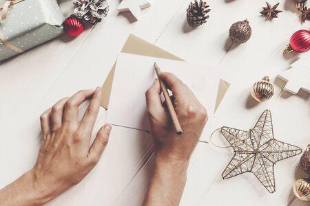 Hände halten Bleistift und schreiben einen Brief an Weihnachtsmann mit Platz für Text. Frohe Weihnachten und guten Rutsch ins neue Jahr. Handwerk und Geschenke und Ornamente auf weißem Holz. Personenwunschliste für Feiertage
