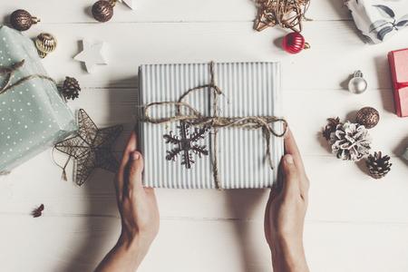 handen met rustieke huidige vak op wit hout met geschenken en ornamenten, bovenaanzicht. vrolijk kerstfeest en gelukkig nieuwjaar plat liggen. seizoensgroeten. fijne feestdagen, kerstkaart