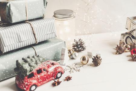 Frohe Weihnachten und guten Rutsch ins neue Jahr. moderne Geschenke, Verzierungen, Autospielzeug mit Baum, Anisstüten und Lichter auf rustikalem weißem hölzernem Hintergrund. saisonale Grüße. Frohe Feiertage, Weihnachtskarte Lizenzfreie Bilder