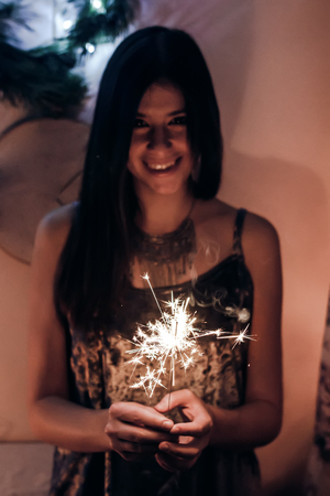 beautiful stylish woman holding  burning sparkler bengal light. glowing shining sparkler closeup in female hand in dark. merry christmas concept. happy new year eve celebration