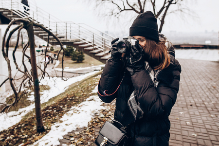 stylish hipster traveler woman holding photo camera and taking picture in winter city street. space for text Archivio Fotografico
