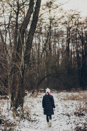 stylish hipster traveler girl with old photo camera exploring in snowy woods in winter. happy woman walking in cold forest. space for text. atmospheric moment. wanderlust