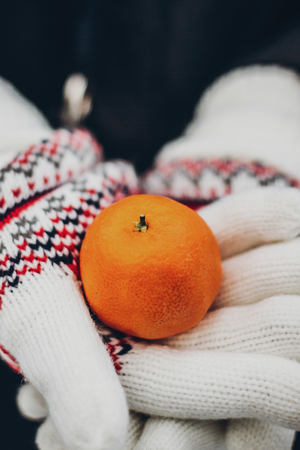 hands in colorful gloves holding mandarine. woman holding tangerine close up in snowy winter park. merry christmas. happy holidays Archivio Fotografico