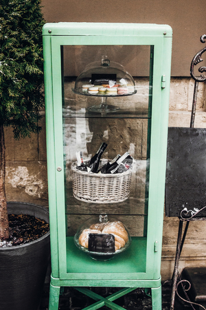 food pantry tray with macaroons and wine in snowy city streets. european city preparing for winter christmas holidays, space for tex