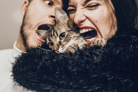 happy stylish hipster family hugging with their cat. man and woman holding kitty and having fun and taking selfie, happy family moments Archivio Fotografico
