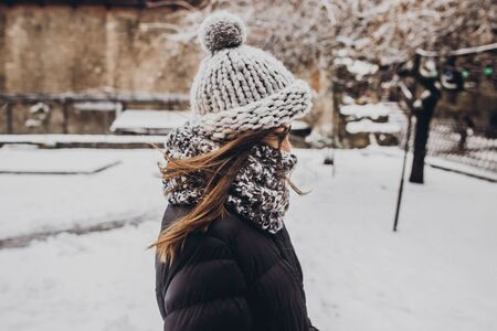 stylish hipster woman in knitted hat standing in snowy city street. beautiful fashionable girl in warm clothes in cold weather with wind. space for text Archivio Fotografico