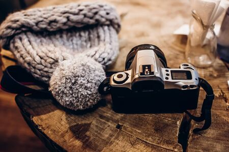 photo camera and warm hat on wooden table in cafe.  winter christmas holidays, space for text Archivio Fotografico