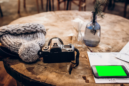 photo camera and warm hat and phone with empty screen on wooden table in cafe.  winter christmas holidays, space for text Archivio Fotografico