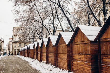 wooden cabins in snow for christmas market. snowy town square in Lviv. european city preparing for winter christmas holidays, space for text