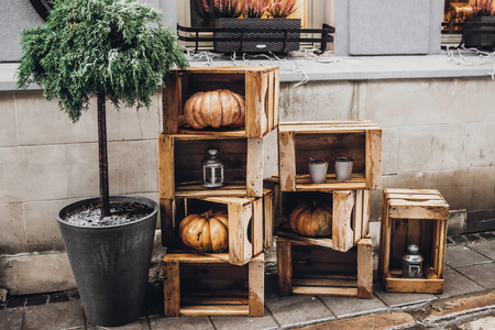 happy halloween. rustic decoration with pumpkins and lanterns in wooden boxes for halloween celebration in european city street. creative arrangement. fall holidays Archivio Fotografico