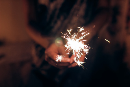 happy new year and merry christmas concept. female hand holding a burning sparkler bengal light. space for text. pyrotechnics concept,  shining fire flame fireworks Archivio Fotografico