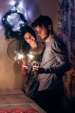 stylish couple holding burning sparkler bengal light and celebrating new year eve at home. merry christmas concept. happy family with fireworks celebrating winter holidays together Archivio Fotografico