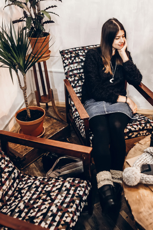 stylish hipster woman relaxing in cafe. girl in warm clothes sitting in modern chair. space for text