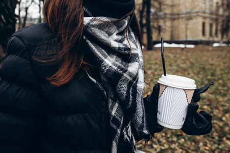 stylish hipster traveler woman holding coffee cup and walking in city street. coffee to go in girl hand in winter Archivio Fotografico