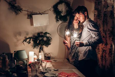 couple élégant tenant la lumière du bengale sparkler brûlant et célébrant la nouvelle année à la maison. concept de Noël joyeux. famille heureuse avec des feux d'artifice célébrant les vacances d'hiver ensemble