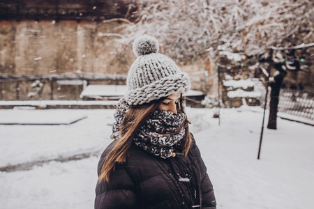stylish hipster woman in knitted hat standing in snowy city street. beautiful fashionable girl in warm clothes in cold snow weather with wind. space for text