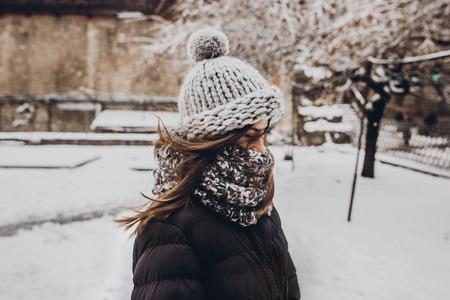 femme élégante hipster en bonnet tricoté debout dans la rue de la ville enneigée. belle fille à la mode dans des vêtements chauds dans la neige froide avec le vent. espace pour le texte Banque d'images