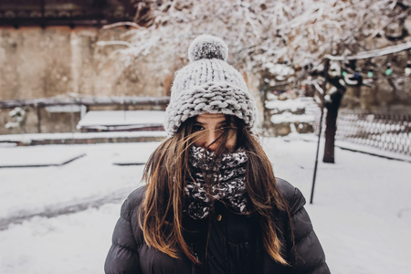 stylish hipster woman in knitted hat standing in snowy city street. beautiful fashionable girl in warm clothes in cold weather with wind. space for text Banque d'images
