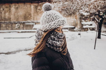 stylish hipster woman in knitted hat standing in snowy city street. beautiful fashionable girl in warm clothes in cold weather with wind. space for text Standard-Bild