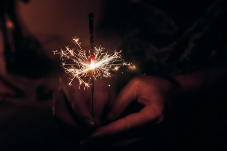 hand holding a burning sparkler bengal light. space for text. burning sparkler closeup in female hand in dark. happy new year and merry christmas concept. happy holidays