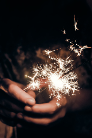 hand holding a burning sparkler firework bengal light. space for text. burning sparkler closeup in female hand in dark. happy new year and merry christmas concept. happy holidays Archivio Fotografico