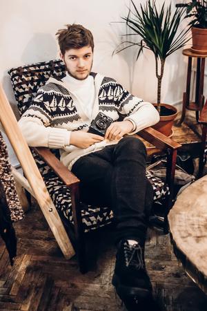 homme élégant hipster avec appareil photo relaxant au café. Guy avec une barbe dans des vêtements chauds, assis sur une chaise moderne. espace pour le texte