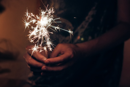 happy new year and merry christmas concept. female hand holding a burning sparkler bengal light. space for text. pyrotechnics concept,  shining fire flame fireworks Stok Fotoğraf