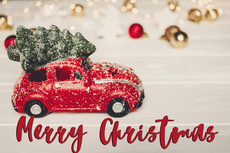 merry christmas text, seasonal greetings card sign. christmas present. red car toy with christmas tree on top on white wood with lights in background,  xmas gift.