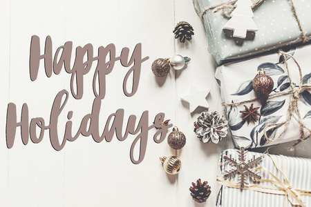 happy holidays text, seasonal greetings card sign. modern christmas flat lay. wrapped presents with ornaments and pine cones anise on rustic white wooden background top view