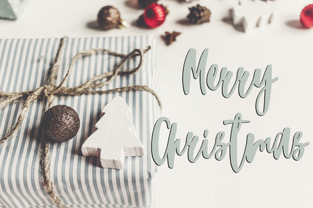 merry christmas text, seasonal greetings card sign. stylish christmas wrapped presents with ornaments and toys on white wooden background top view