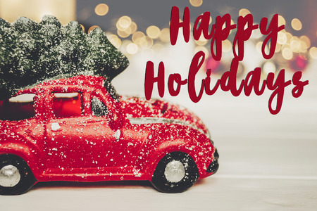 happy holidays text, seasonal greetings card sign. red car toy with christmas tree on top on white wood with lights in background