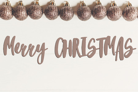 merry christmas text, seasonal greetings card sign. flat lay. glitter golden christmas ornaments  frame or border on white wooden background top view Stock Photo