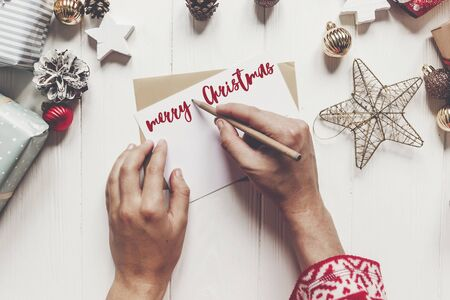 merry christmas text, seasonal greetings card sign. hands holding pencil and making wish list or greeting  and paper with christmas decorations and ornaments and presents on white wood. space for text Stock Photo