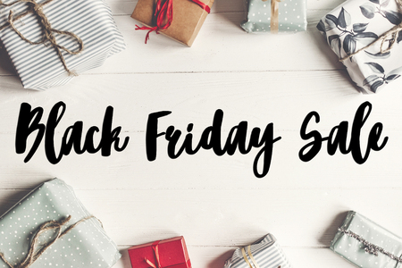 black friday sale text. big sale offer discount sign on wrapped present boxes on white wooden background top view, space for text. flat lay, shopping concept Stock Photo