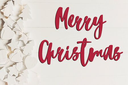 merry christmas text, seasonal greetings card sign. minimalistic  flat lay. simple wooden white christmas ornaments trees and stars frame or border, top view Stock Photo