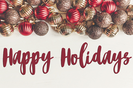 happy holidays text, seasonal greetings card sign. christmas flat lay. red and gold christmas ornaments  frame or border on white wooden background top view Stock Photo